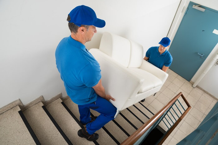 Liefermänner tragen Sofa auf Treppe